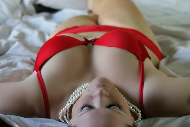Sexy Frau auf Bett in roten Dessous